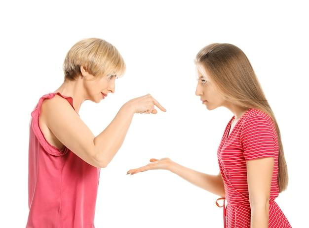 Ritratto di litigare madre e figlia sulla superficie bianca