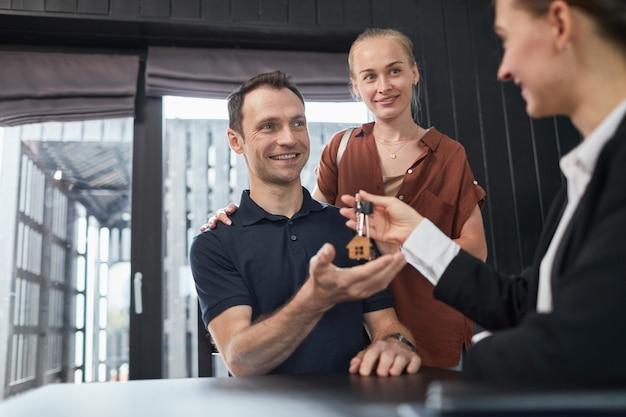 Ritratto di agente immobiliare che dà le chiavi alla coppia con particolare attenzione al portachiavi della casa, copia spazio