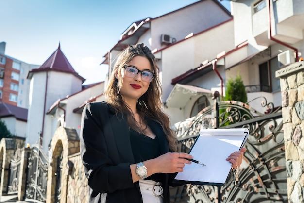 Ritratto di una donna di agente immobiliare in piedi davanti a una nuova casa. concetto di vendita o affitto