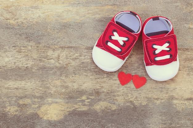 Ritratto di scarpe da bambino rosse carine e due cuori rossi su un tavolo di legno