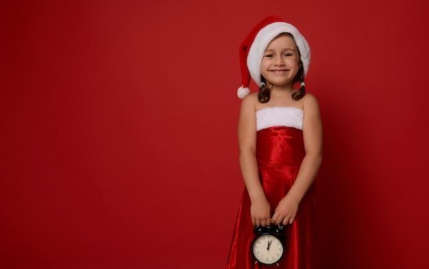 Ritratto su sfondo rosso della bambina carina, adorabile bambino in abito di carnevale di babbo natale, con in mano una sveglia e sorridente con un bel sorriso a trentadue denti che guarda l'obbiettivo. concetto di natale, copia spazio