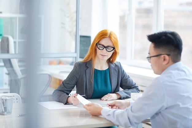 Ritratto di dai capelli rossi responsabile delle risorse umane intervistando il giovane per posizione di lavoro in ufficio, copia dello spazio