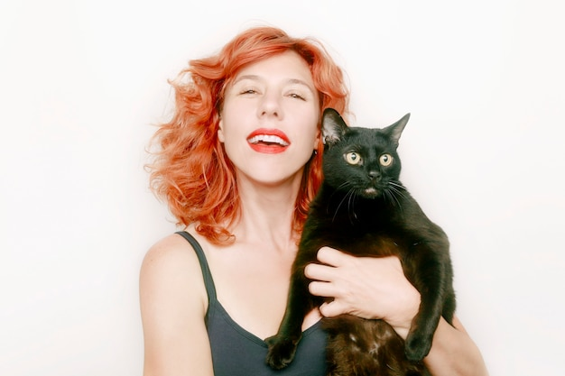 Ritratto di donna dai capelli rossi con grande gatto nero