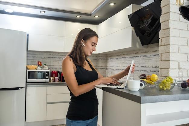 Ritratto di ragazza felice rilassata in cuffie che studia o ascolta musica in cucina. stile di vita sano