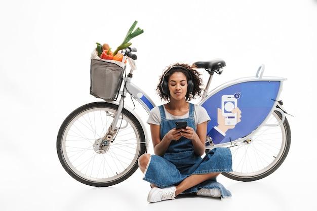 Ritratto di donna rilassata che tiene il cellulare mentre è seduto vicino alla bicicletta con la borsa della spesa isolata su un muro bianco