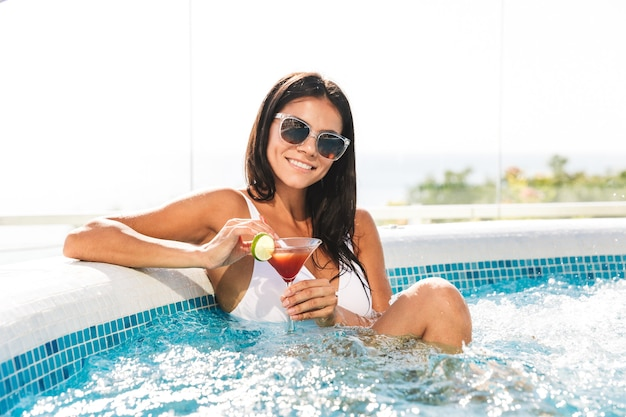 Ritratto di rilassante bella donna in costume da bagno bianco e occhiali da sole, prendere il sole e bere cocktail nella vasca idromassaggio jacuzzi durante le vacanze