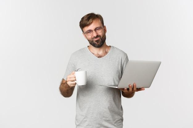 Ritratto di riluttante uomo barbuto in maglietta grigia e occhiali