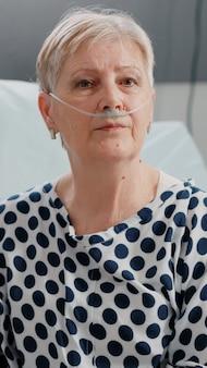 Ritratto di donna in pensione con tubo di ossigeno nasale e ossimetro