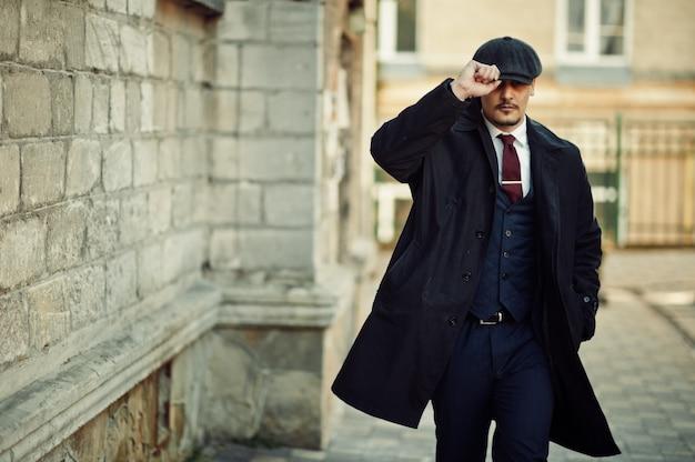 Ritratto di uomo d'affari arabo inglese retrò anni '20 che indossa cappotto scuro, abito, cravatta e berretto piatto.