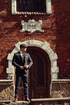 Ritratto di retro 1920s arabo inglese uomo d'affari che indossa abito scuro, cravatta e berretto piatto in piedi contro la vecchia casa di mattoni 1898 anno.