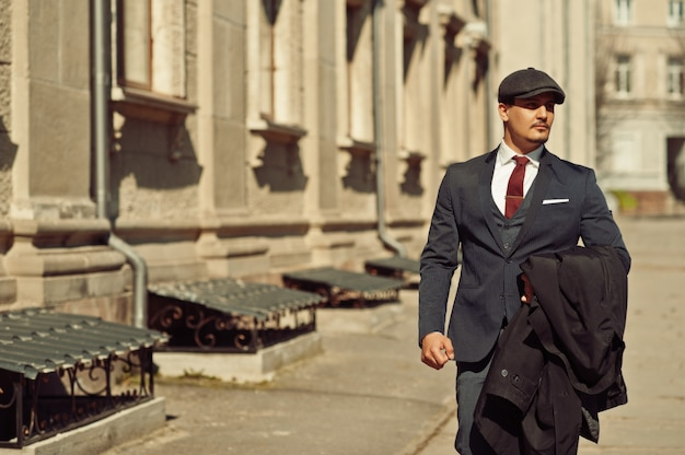 Ritratto di un uomo d'affari arabo inglese retrò degli anni '20 che indossa abito scuro, cravatta e berretto piatto camminando per le vecchie strade.