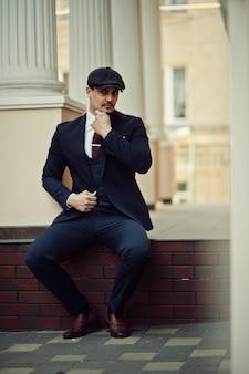 Ritratto di un uomo d'affari arabo inglese retrò anni '20 che indossa abito scuro, cravatta e berretto piatto.