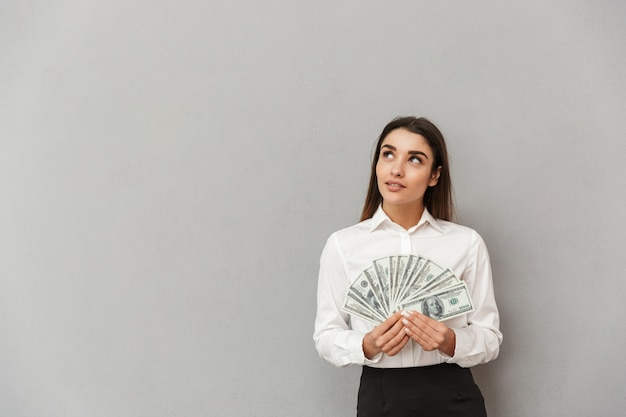 Ritratto di donna ricca di ufficio con lunghi capelli castani in abbigliamento da lavoro, alzando lo sguardo su copyspace e tenendo la ventola di denaro, isolato sopra il muro grigio