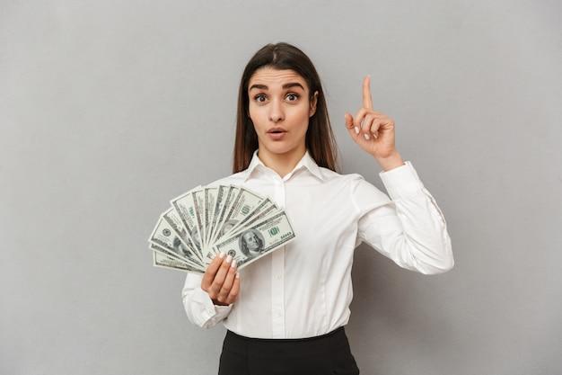 Ritratto di donna ricca ufficio con lunghi capelli castani in abbigliamento da lavoro puntare il dito verso l'alto su copyspace e tenendo la ventola di denaro, isolato su muro grigio