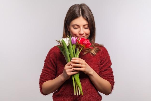 Ritratto di una bella ragazza bruna romantica che odora il mazzo di fiori e sorride con piacere