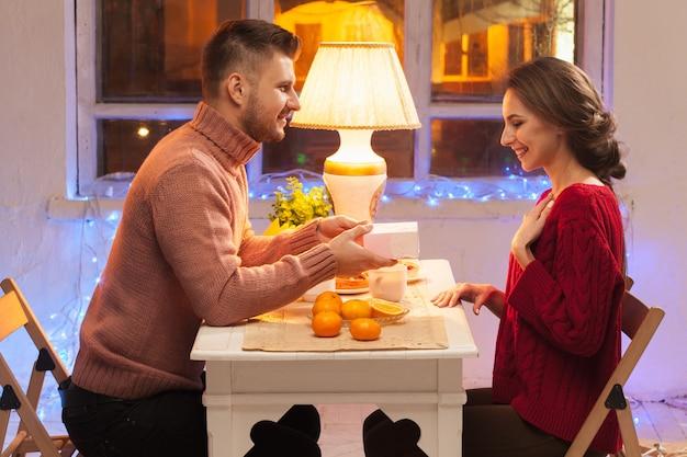 Ritratto di coppia romantica alla cena di san valentino con regalo