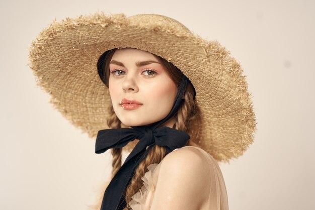 Ritratto di una ragazza romantica in un vestito e un cappello di paglia con un nastro nero
