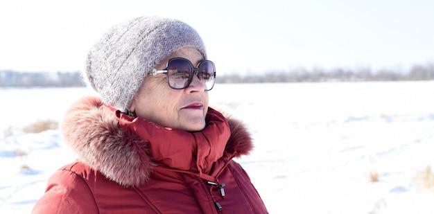 Ritratto di donna senior russa che guarda lontano contro il campo nevoso