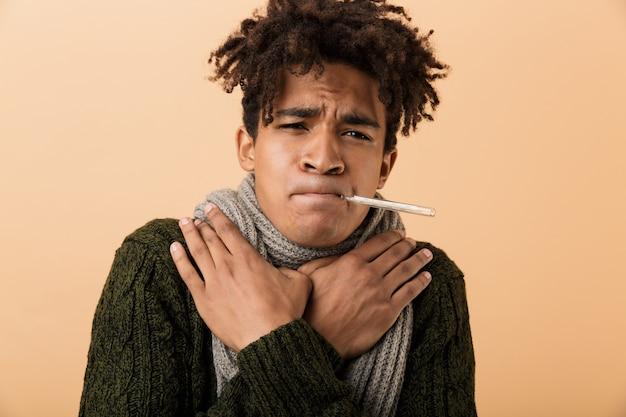 Ritratto di ragazzo afroamericano triste che indossa un maglione e sciarpa afferrando la gola con il termometro in bocca, isolato sopra il muro beige