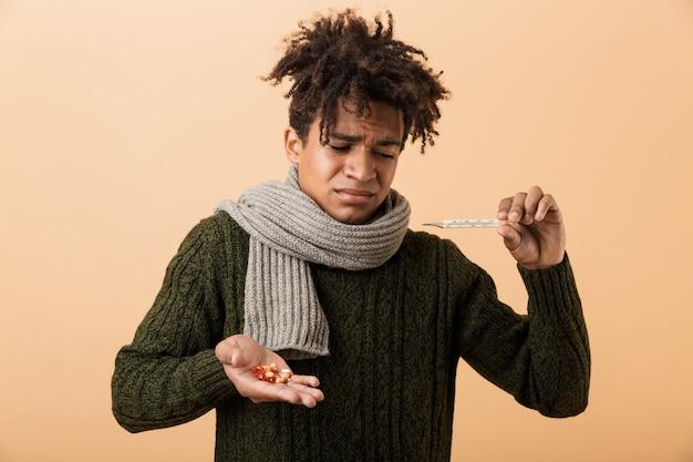 Ritratto di un uomo africano triste vestito in abiti autunnali isolati su muro beige, mostrando capsule di pillole, tenendo il termometro