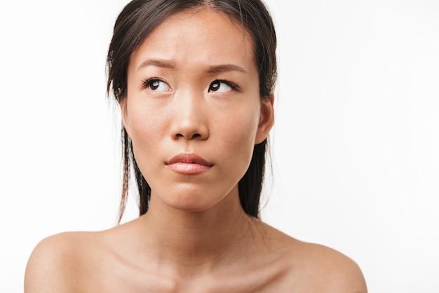 Ritratto di una giovane bella donna asiatica triste confusa in posa isolata sul muro bianco