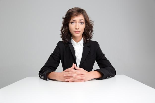 Ritratto di donna piuttosto riccia delusa triste in giacca nera