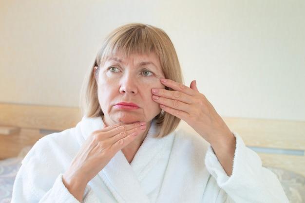 Ritratto triste donna anziana sullo sfondo della sua camera da letto. le sue mani toccano le rughe del viso. concetto anti età, sanità e cosmetologia, stanchezza, pensiero vecchiaia e malattia