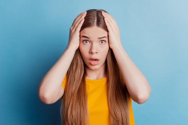 Ritratto di una ragazza nervosa frustrata triste con le mani a testa a bocca aperta su sfondo blu
