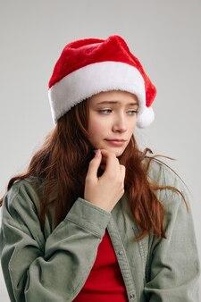 Ritratto di una ragazza triste in un cappello da festa con un pompon e primo piano vista ritagliata
