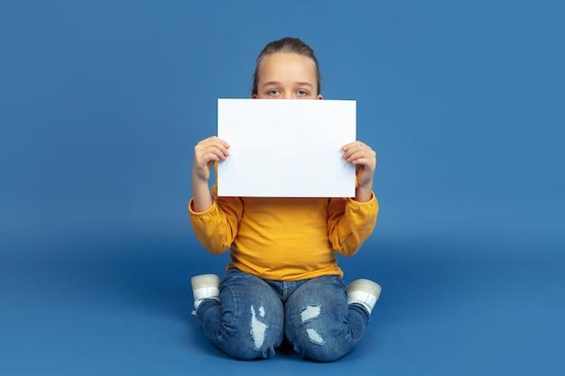 Ritratto di triste bambina seduta isolata su sfondo blu per studio. come ci si sente ad essere autistici. problemi moderni, nuova visione dei problemi sociali. concetto di autismo, infanzia, assistenza sanitaria, medicina.