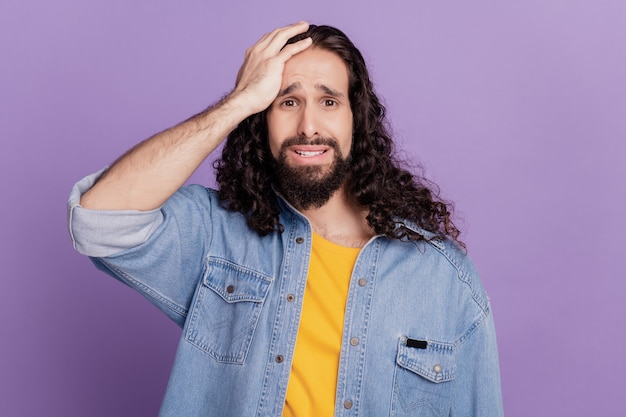 Il ritratto di un uomo triste ha sbagliato la testa della mano di fallimento su sfondo viola