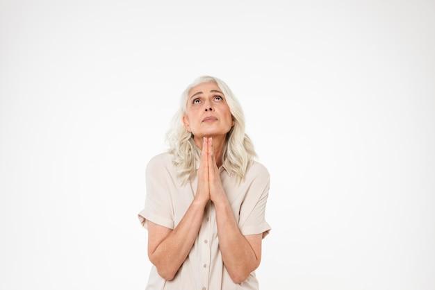 Ritratto di una donna matura triste che prega e che osserva in su