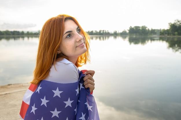 Ritratto di triste ragazza dai capelli rossi con bandiera nazionale degli stati uniti sulle sue spalle. giovane donna che celebra il giorno dell'indipendenza degli stati uniti.