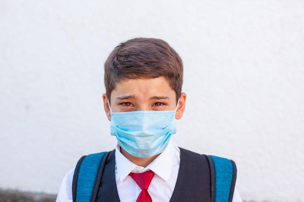 Ritratto di un adolescente scolaro triste in una mascherina medica