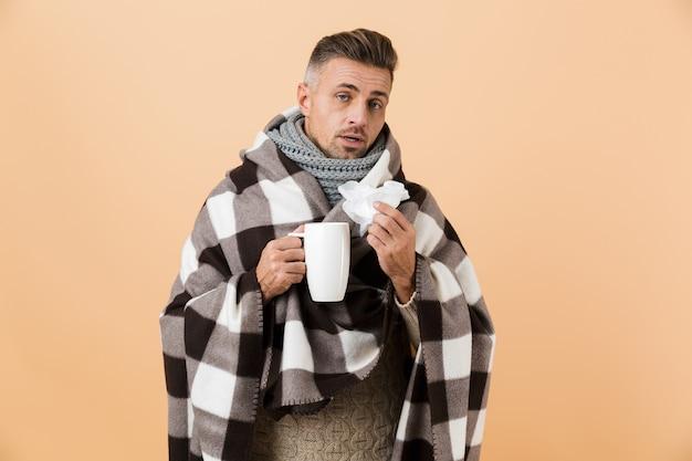 Ritratto di un triste uomo malato avvolto in una coperta in piedi isolato sopra il muro beige, con in mano una tazza e un tovagliolo