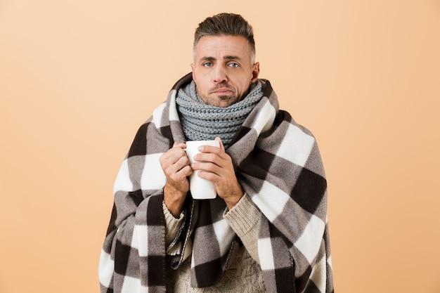 Ritratto di un uomo malato triste avvolto in una coperta in piedi isolata sopra il muro beige, che tiene tazza con tè caldo