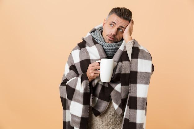 Ritratto di un uomo malato triste avvolto in una coperta in piedi isolata sopra il muro beige, mostrando il termometro