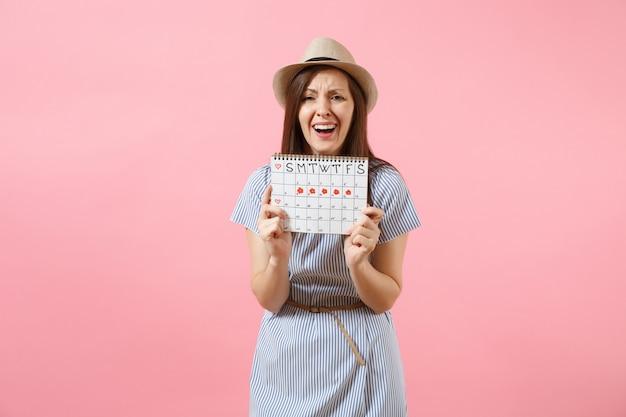 Ritratto triste malattia sconvolta donna in abito blu che tiene il calendario dei periodi per il controllo dei giorni delle mestruazioni, mal di addome isolato su sfondo rosa. concetto medico, sanitario, ginecologico. copia spazio