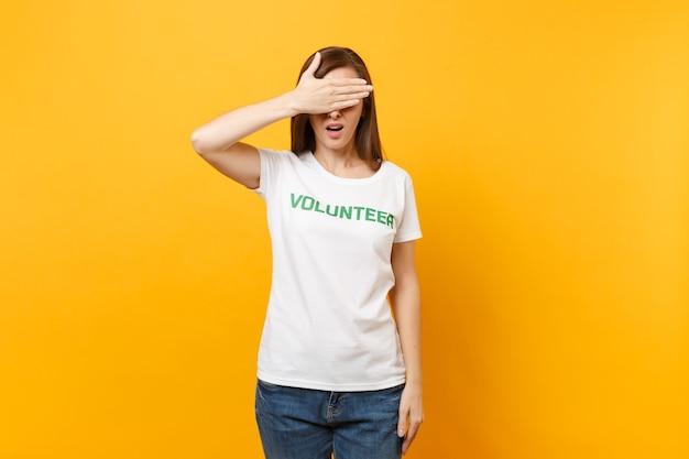Ritratto di giovane donna sconvolta sconvolta triste in maglietta bianca con iscrizione scritta volontario titolo verde isolato su sfondo giallo. aiuto volontario di assistenza gratuita, concetto di lavoro di grazia di carità.