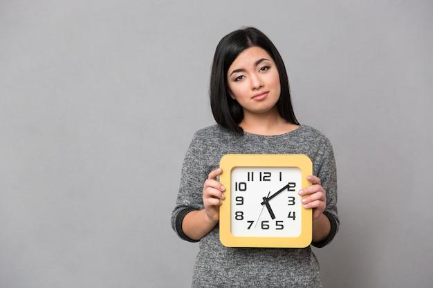 Ritratto di una donna triste che tiene orologio da parete sopra il muro grigio