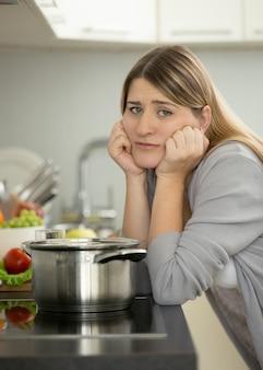Ritratto di donna triste appoggiata al tavolo in cucina mentre cucina