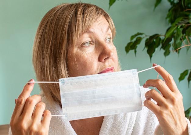 Ritratto di una donna triste che indossa una mascherina medica a causa dell'epidemia di coronavirus