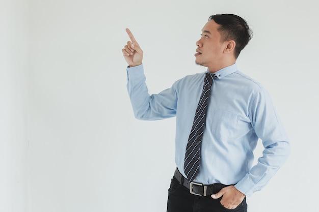 Ritratto di uomo di vendita che indossa camicia blu e cravatta che punta su uno spazio vuoto per la pubblicità space