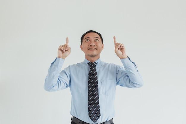 Ritratto di uomo di vendita che indossa camicia blu e cravatta rivolta verso l'alto su uno spazio vuoto per pubblicità o idea