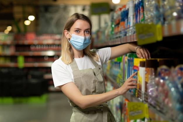 Ritratto di commessa, in maschera protettiva donna sorridente e guardando la fotocamera in un supermercato. venditore femminile amichevole piacevole che sta nel deposito fra le file. operaio con le braccia incrociate