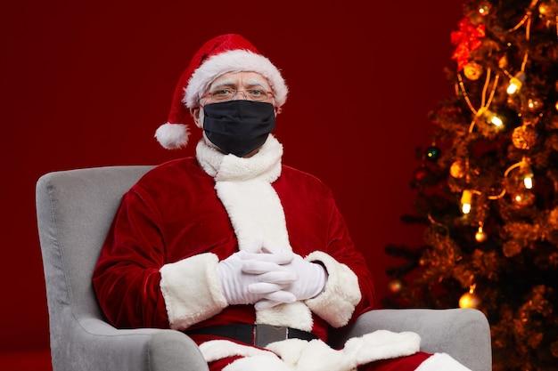 Ritratto di babbo natale in costume rosso che celebra il natale in maschera protettiva durante la pandemia