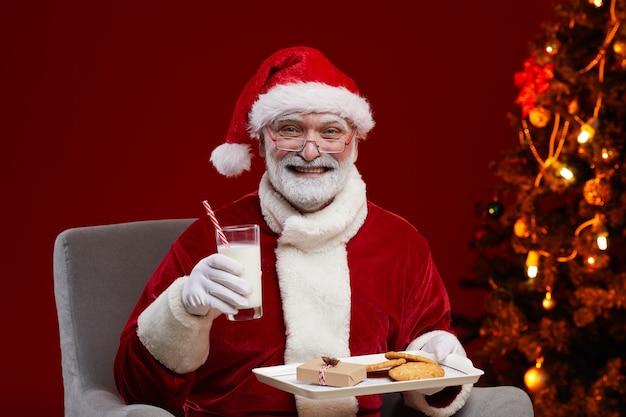Ritratto di babbo natale seduto sulla poltrona con latte e biscotti sorridente