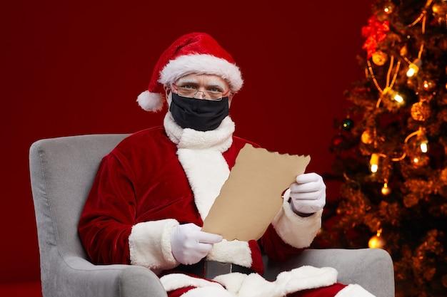 Ritratto di babbo natale che indossa la maschera protettiva leggendo una lettera mentre è seduto sulla poltrona