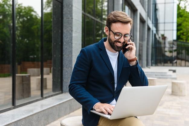 Ritratto di uomo d'affari soddisfatto indossando occhiali da vista parlando al cellulare e utilizzando laptop mentre è seduto all'aperto vicino all'edificio