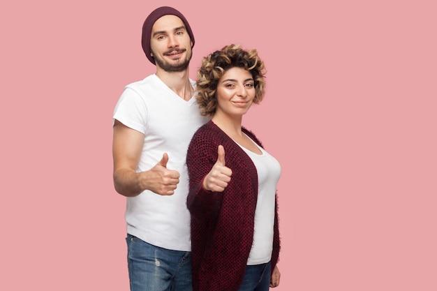 Ritratto di coppia soddisfatta di amici in stile casual in piedi, abbracciando e mostrando il pollice in alto segno, guardando la fotocamera. isolato, interno, girato in studio, sfondo rosa